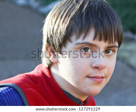 horizontal orientation close up portrait of smiling boy with autism and down's syndrome in outdoor setting / Dual Diagnosis - stock photo