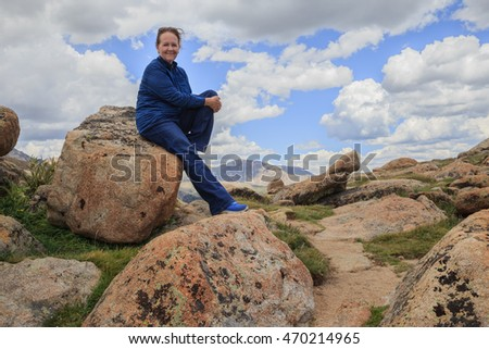 horizontal orientation color image of a single, happy, older woman hiker stopping to rest on a large boulder against a cloudy blue sky / Senior Woman Hiking in the Rockies