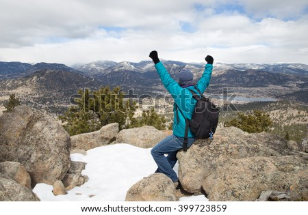 horizontal orientation color image of a single woman hiker in a power pose, celebrating the Rocky Mountain Views at Trail's end in Winter / Woman Hiker in Power Pose at 9,000 feet - stock photo