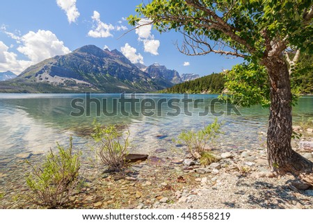 horizontal orientation color image of St. Mary Lake inside Glacier National Park, Montana with clear water at the shoreline / St. Mary Lake in Glacier National Park, Montana USA - stock photo