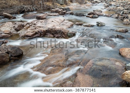 horizontal orientation color image, taken with a very slow shutter speed, to show the movement of water along a rocky creek in Colorado / Pure Water in a Colorado Creek in Winter - stock photo