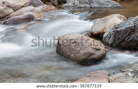 horizontal orientation color image, taken with a very slow shutter speed, to show the movement of water along a rocky creek in Colorado / Waterfalls and Boulders in the Rockies - stock photo