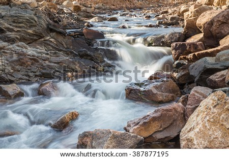 horizontal orientation color image, taken with a very slow shutter speed, to show the movement of water along a rocky creek in Colorado /  Winter in the Rockies with gentle flowing waterfalls - stock photo