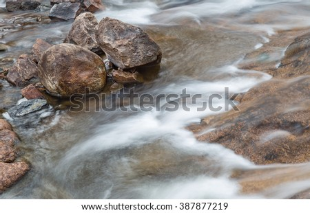 horizontal orientation color image, taken with a very slow shutter speed, to show the movement of water along a rocky creek in Colorado / Rocky Creek with Flowing Water