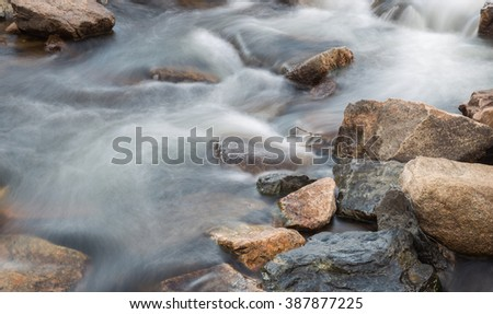 horizontal orientation color image, taken with a very slow shutter speed, to show the movement of water along a rocky creek in Colorado /  Flowing Creek and Multi colored Rocks - stock photo