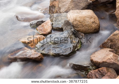 horizontal orientation color image, taken with a very slow shutter speed, to show the movement of water along a rocky creek in Colorado /  Rocky Creek and Water Flow - stock photo