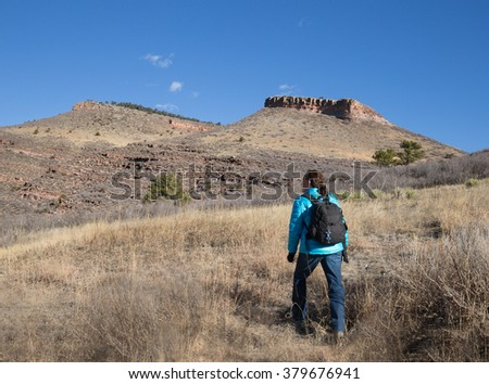 horizontal orientation color image with a single woman hiker in bright clothing in the foreground, and blue skies and rocky mountains in the background / Woman Hiker on a sunny winter day - stock photo
