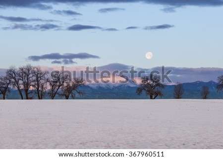horizontal orientation color image with fresh snow in the foreground, and first morning light on the Rocky Mountains with a full moon present / Full Moon and First Morning Light over the Rockies - stock photo