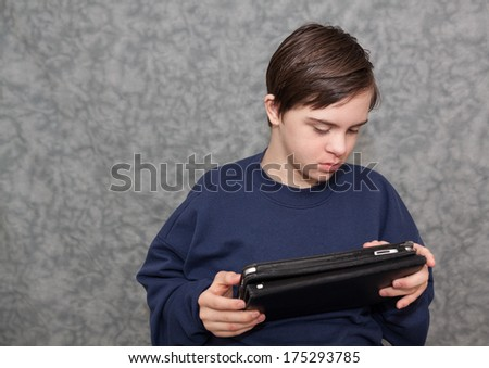 horizontal orientation of a boy with autism and down's syndrome sitting down, holding a tablet device in both hands as he looks at the screen / Apps for Visual Learners - stock photo