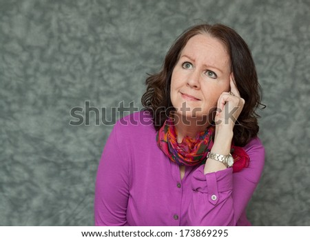 horizontal orientation of a woman in brightly colored business attire with a questioning look as she tries to remember something / Trying to Remember - stock photo