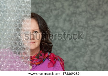 horizontal orientation of a woman in brightly colored business attire with a slight smile and one half of her face blurred by a textured surface / Hidden from View - stock photo