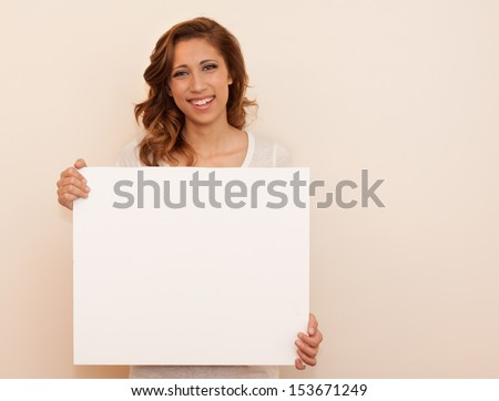 horizontal orientation of happy smiling teenage girl holding a blank, white, sign with copy space and neutral background / Pleased to Meet You! - stock photo