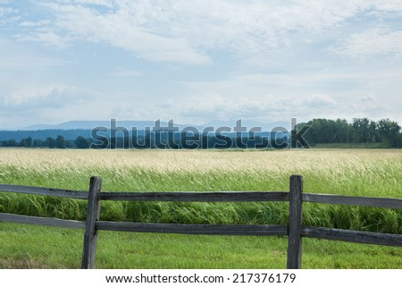 horizontal orientation of open fields and vintage wooden fence in the foreground, with mountains, sky and trees in the background / Northern Idaho Scenery - stock photo