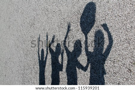 horizontal orientation of shadows of 4 kids playing together with gray gravel background and copy space / Shadow Play - stock photo