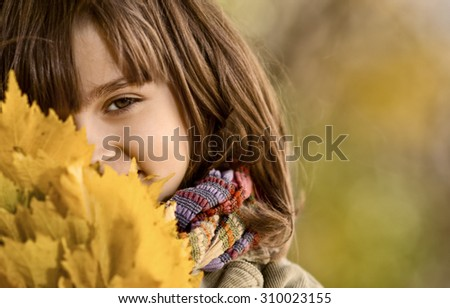 horizontal photo,  beautiful little girl hold many yellow leaf, autumnal portrait - stock photo