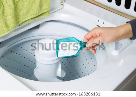 Horizontal photo female hand putting in powdered soap into washing machine for laundry  - stock photo