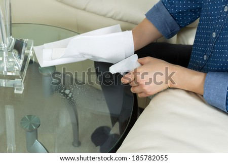 Horizontal photo female hand spraying cleaning solution, from spray bottle, onto dirty glass round end table with paper towels and sofa with partial lamp in background  - stock photo