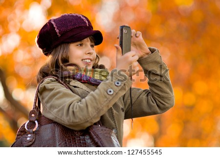 horizontal photo, happy beautiful little girl take a photograph on  mobile phone, autumnal portrait - stock photo