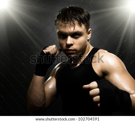 horizontal photo  muscular young  guy street-fighter,  aggression look, hard light - stock photo