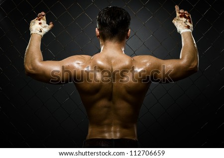 horizontal photo  muscular young  guy street-fighter,  athletic  back, hard light - stock photo