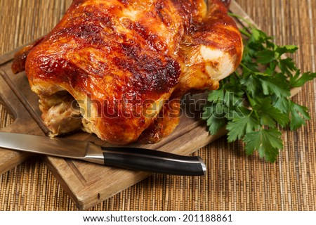 Horizontal photo of a freshly oven roasted Whole Chicken on traditional rustic cutting board with knife and parsley on side - stock photo