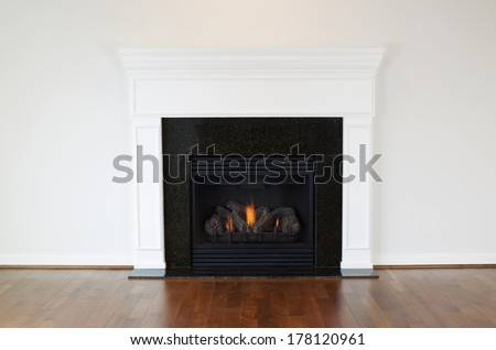 Horizontal photo of a natural gas fireplace with a white mantle and cherry wood floors  - stock photo