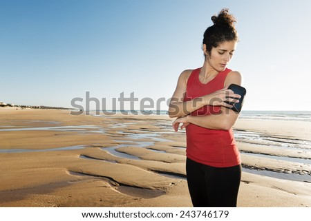 Horizontal photo of a young woman preparing her armband to run on the beach. - stock photo