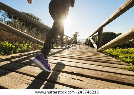 Horizontal photo of a young woman running on the path leading to the beach. - stock photo