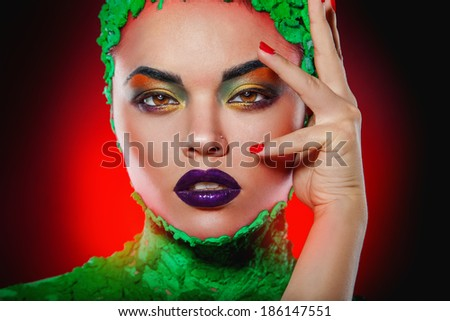 Horizontal photo of attractive woman with creative makeup in studio