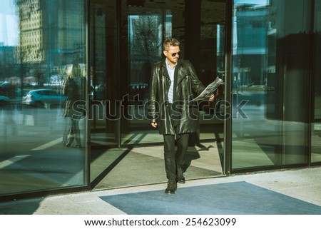 Horizontal photo of beautiful adult male model in sunglasses and leather jacket with newspaper in hand outdoors - stock photo