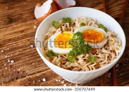 Horizontal photo of chinese soup inside white bowl placed on wooden board. Two slices of soft boiled egg are on noodles. Chopsticks, salt and egg shells are around.  - stock photo