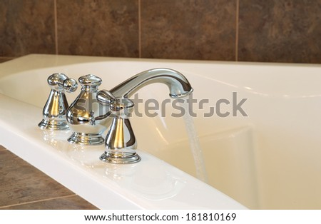 Horizontal photo of chrome faucet running water into soaking tub in master bathroom  - stock photo