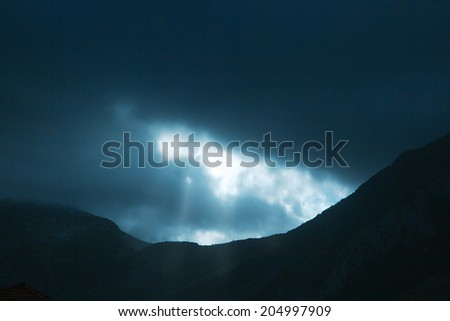 Horizontal Photo of dramatic rays of light pushing up through clouds - stock photo