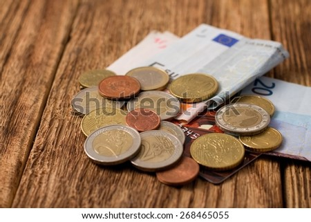 Horizontal photo of euro Coins, bills and credit card on one heap placed on old worn wooden board with significant grooves. - stock photo
