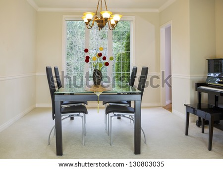 Horizontal photo of family formal dining room with daylight coming through large windows in background