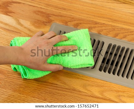 Horizontal photo of female hand cleaning outside grill plate of heater floor vent with Red Oak Floors in background  - stock photo