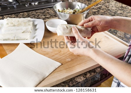 Horizontal photo of female hands making rolling wrap to make Chinese Spring Roll - stock photo