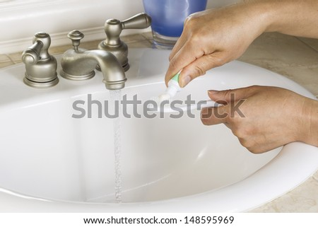 Horizontal Photo of female hands putting tooth paste on toothbrush with white bathroom sink, blue cup and running faucet in background   - stock photo