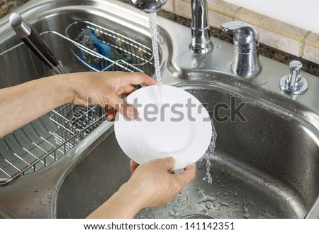 Horizontal photo of female hands rinsing off a small white dinner plate with kitchen sink and running faucet in background - stock photo