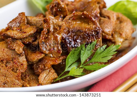 Horizontal photo of Korean Barbequed Pork, parsley in white bowl with chop sticks and cloth napkin on side - stock photo