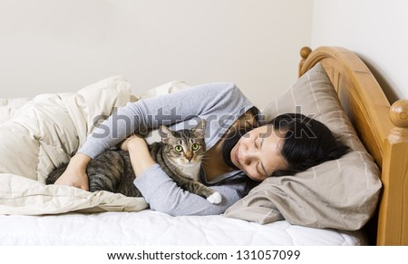 Horizontal photo of mature woman, lying head down in pillow, while hold her family cat in bed - stock photo