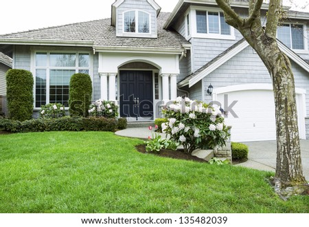Horizontal photo of modern home in North American Suburbs with plush green grass, rhododendron and tulips flower in mid spring season - stock photo