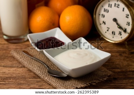 Horizontal photo of Morning with white yogurt and fruit in separated white bowls placed on jute cloth with spoon next to food and alarm clock, oranges plus glass with milk. - stock photo