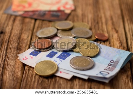 Horizontal photo of Pile of Euro bills and coins plus two credit cards placed on old worn wooden board - stock photo