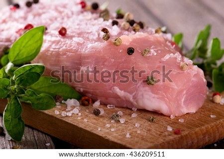 Horizontal photo of pork meat. Big portion of pork meat on chopping board. Meat with herbs on old wooden board with worn grey color. Color pepper and grained salt with oregano on pork.