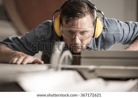 Horizontal photo of professional saw operator preparing ideal board - stock photo
