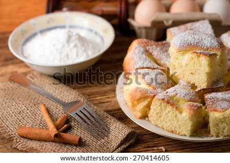 Horizontal photo of Several portions of curd cake on white plate next two fork and cinnamon on jute cloth plus eggs and powder sugar in a bowl in background - stock photo