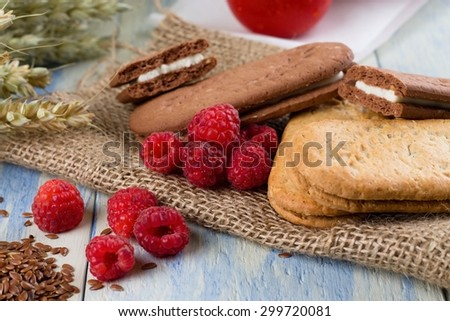 Horizontal photo of several raspberries in front of few cereal whole wheat creamy biscuits on jute burlap cloth. Grains, linseeds and tomatoes are around on light blue wooden board. - stock photo
