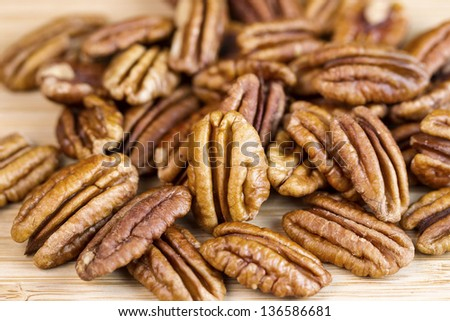 Horizontal photo of slightly roasted pecan nuts with focus of standing pecan in front of pile on natural wood - stock photo
