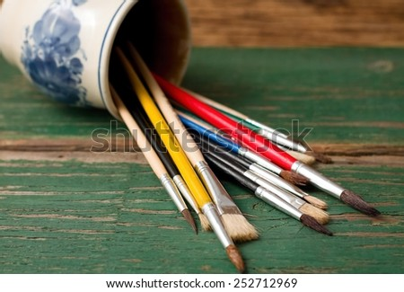 Horizontal photo of spilled jar full of color paintbrushes on green old worn wooden board. - stock photo